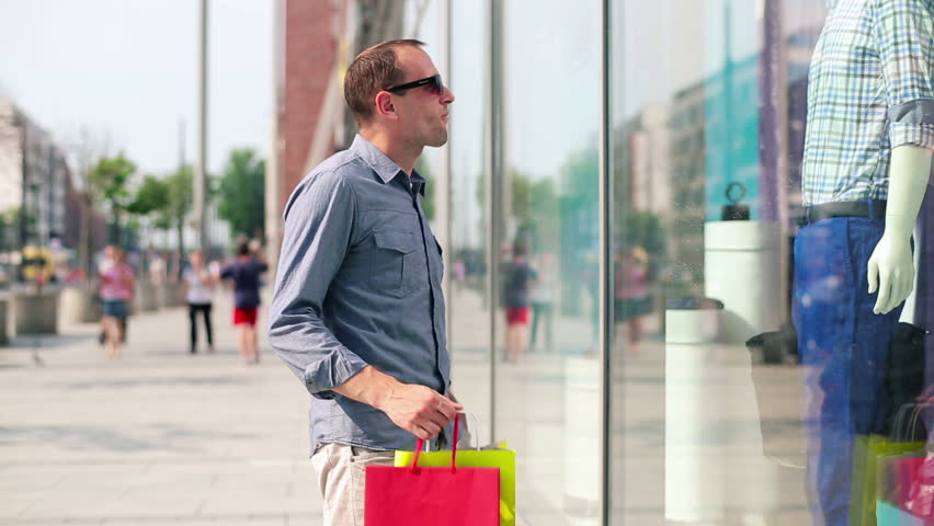 A man looking in shop window to represent how social media should entice readers to your website
