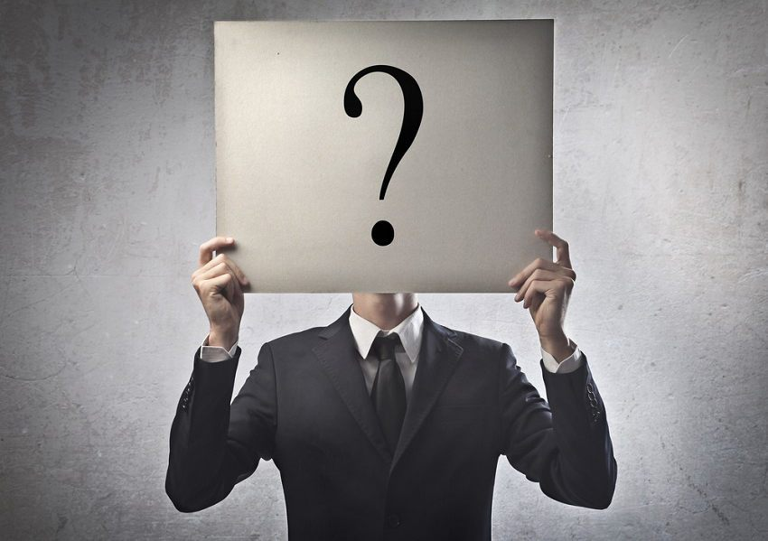 A man holding a question mark over his head to show how social media can be used to make more detailed buyer personas